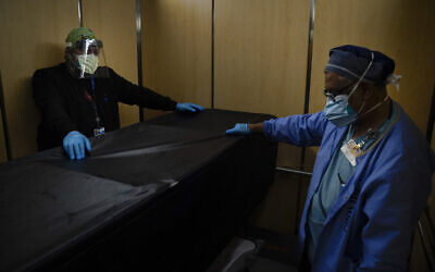 In this Jan. 9, 2021, file photo, transporters Miguel Lopez, right, Noe Meza move a body of a COVID-19 patient to a morgue at Providence Holy Cross Medical Center in the Mission Hills section of Los Angeles.(AP Photo/Jae C. Hong, File)