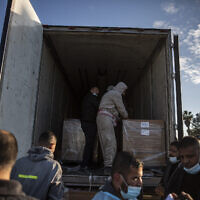 Palestinian workers unload a truck from 20,000 doses of Russian-made Sputnik V vaccine upon its arrival to Gaza Strip, at the Rafah crossing border with Egypt, February 21, 2021. (AP Photo/Khalil Hamra)
