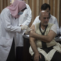 Former Palestinian health minister Jawad al-Tibi receives a shot of the COVID-19 Russian-made Sputnik V vaccine, in Gaza City, Febuary 22, 2021. (AP Photo/Khalil Hamra)