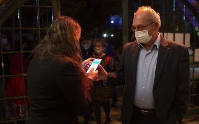 A man presents his Green Pass, proof that he is vaccinated against the coronavirus, on opening night at the Khan Theater for a performance where all guests were required to show proof of vaccination or full recovery from the virus, in Jerusalem, February 23, 2021. (AP/Maya Alleruzzo)