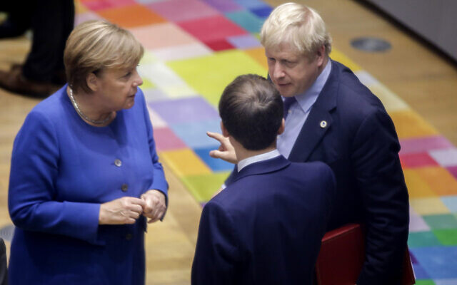 British Prime Minister Boris Johnson, right, speaks with German Chancellor Angela Merkel, left, and French President Emmanuel Macron during a round table meeting at an EU summit in Brussels, October 17, 2019. (AP Photo/ Olivier Matthys, Pool)