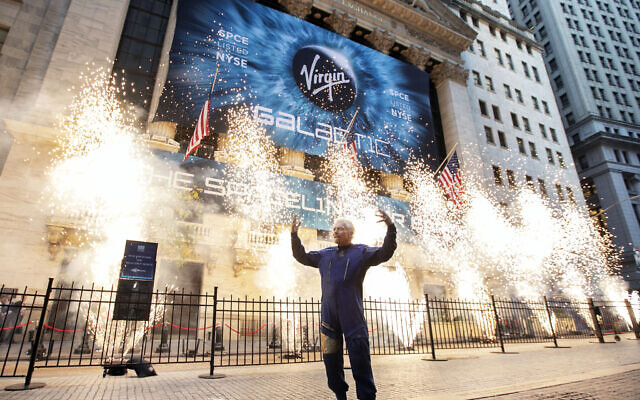Sir Richard Branson, founder of Virgin Galactic, poses for a photo outside the New York Stock Exchange as fireworks are exploded before his company's IPO, performed via a reverse merger with a SPAC, on Monday, Oct. 28, 2019. (AP/Richard Drew)