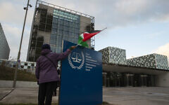 A demonstrator poses with a Palestinian flag outside the International Criminal Court, ICC, during a rally urging the court to prosecute Israel's army for war crimes, in The Hague, Netherlands, November 29, 2019. (AP/Peter Dejong)