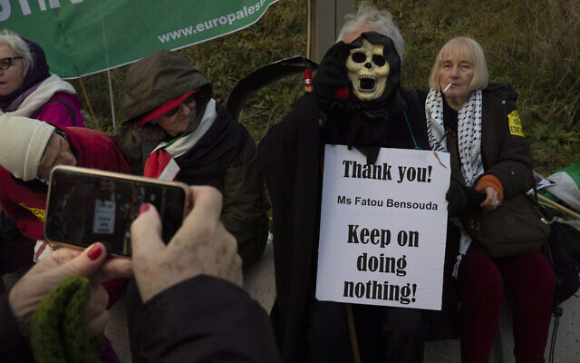 A woman takes a picture of the Grim Reaper holding a sign referring to Chief Prosecutor Fatou Bensouda during a demonstration outside the International Criminal Court, ICC, urging the court to prosecute Israel's army for war crimes in The Hague, Netherlands, Friday, Nov. 29, 2019. (AP/Peter Dejong)