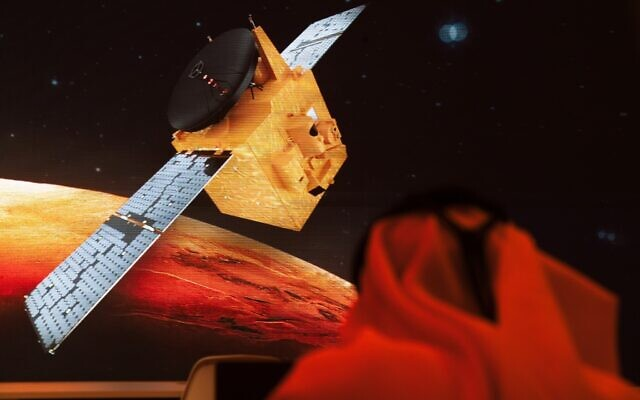 An Emirati television journalist works on a script as a graphic showing the Emirates' Hope space probe to Mars flashes past him on a screen, at the Mohammed bin Rashid Space Center in Dubai, United Arab Emirates, July 19, 2020. (Jon Gambrell/AP)