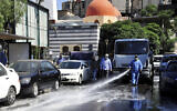 A Syrian worker disinfects a street to prevent the spread of coronavirus in Damascus, Syria, August 3, 2020. (SANA via AP)