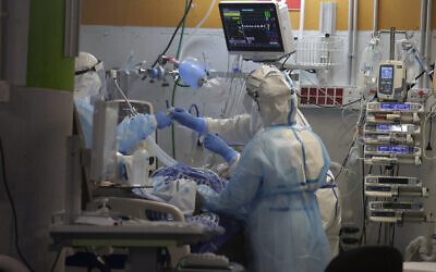 Medical professionals in full protective equipment tend to an elderly man on a ventilator in the critical care coronavirus unit at Sheba Medical center in Ramat Gan, Wednesday, Sept. 30, 2020 (AP Photo/Maya Alleruzzo)