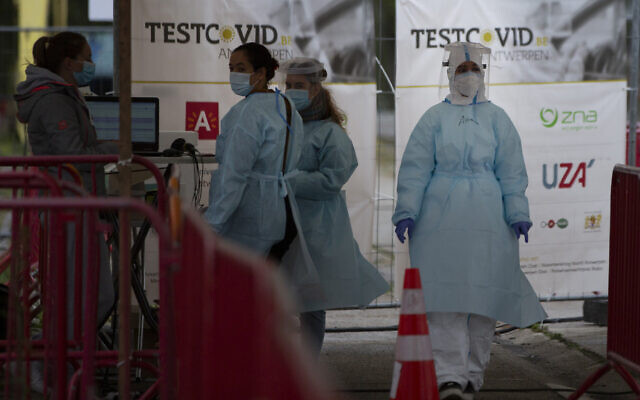 Health care workers wait to administer nose-swab tests at the mobile COVID-19 testing site in Antwerp, Belgium, Oct. 20, 2020 (AP Photo/Virginia Mayo)