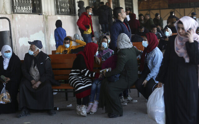 Illustrative: Passengers wait for their passports to be processed so they can cross the Rafah border to the Egyptian side, in Rafah, Gaza Strip, November 24, 2020. (AP Photo/Adel Hana)