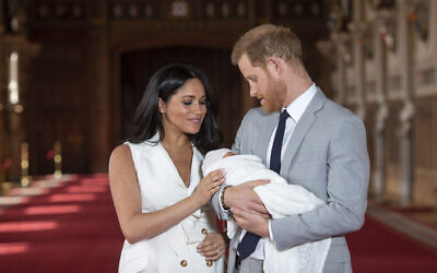 Britain's Prince Harry and Meghan, Duchess of Sussex, pose during a photocall with their then-newborn son Archie, in St George's Hall at Windsor Castle, Windsor, south England, on May 8, 2019. (Dominic Lipinski/ Pool via AP)