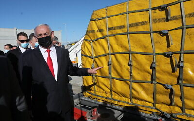 Prime Minister Benjamin Netanyahu attends the arrival of over 100,000 doses of the Pfizer coronavirus vaccine, at Ben Gurion Airport on December 9, 2020. (Abir Sultan/Pool Photo via AP)