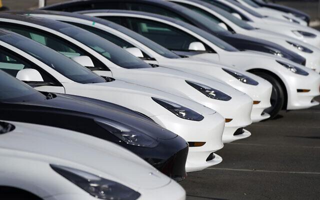 A long row of unsold 2021 Model 3 sedans sits at a Tesla dealership, December 27, 2020, in Littleton, Colorado. (AP Photo/David Zalubowski)