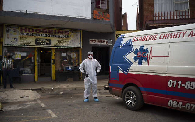 Paramedic Clive Maleso stands next to a Saaberie Chishty ambulance before transferring a COVID-19 patient from his home to the hospital in Lenasia, South Africa, Thursday, Jan. 7, 2021 (AP Photo/Bram Janssen)