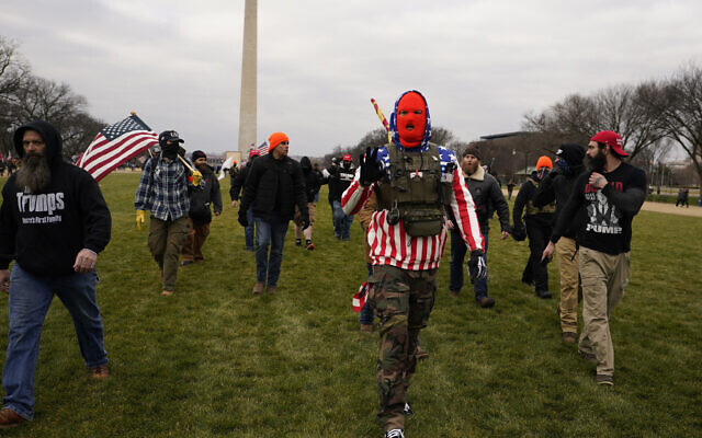 In this January 6, 2021 photo, people march with those who say they are members of the Proud Boys as they attend a rally in Washington in support of President Donald Trump. (AP Photo/Carolyn Kaster)