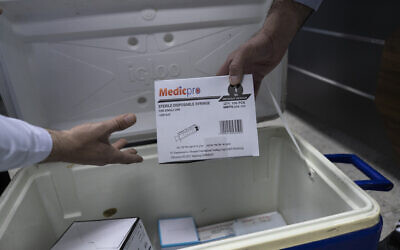 Illustrative: Palestinian medics unpack Moderna COVID-19 vaccines and supplies that are designated for front-line medical workers, at the health ministry, in the West Bank city of Bethlehem, February 3, 2021. The Palestinian Authority has administered its first known coronavirus vaccinations after receiving several thousands of doses of the Moderna vaccine from Israel. (AP Photo/Nasser Nasser)