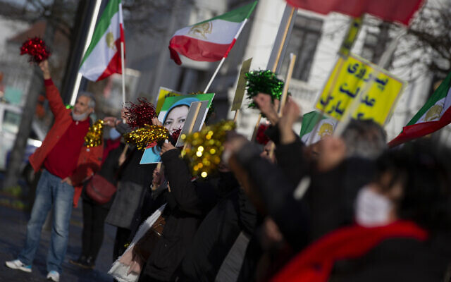 People wave flags after the trial of four persons, including an Iranian diplomate and Belgian-Iranian couple at the courthouse in Antwerp, Belgium, February 4, 2021. (AP Photo/Virginia Mayo)