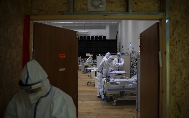 Medical personnel wearing protective equipment treat COVID-19 patients in an intensive care ward for coronavirus patients at Ziv Medical Center in the northern Israeli city of Safed, Feb. 7, 2021. (AP Photo/Oded Balilty)