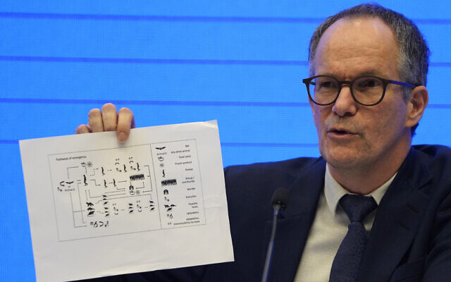 Peter Ben Embarek of the World Health Organization team holds up a chart showing pathways of transmission of the virus during a joint press conference held at the end of the WHO mission in Wuhan in central China's Hubei province on Feb. 9, 2021. (AP Photo/Ng Han Guan)