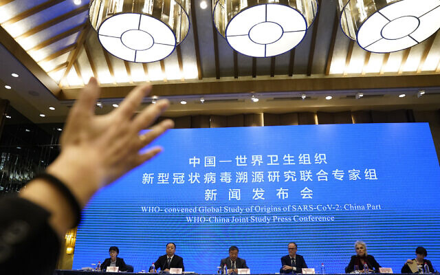 A journalist raises her hand to ask a question at the WHO-China Joint Study Press Conference held at the end of the World Health Organization mission in Wuhan, China, Tuesday, Feb. 9, 2021. (AP Photo/Ng Han Guan)