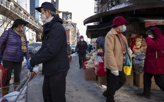 Shoppers walk with their purchases, Monday, Feb. 8, 2021, in the Chinatown neighborhood of New York. (AP Photo/Mark Lennihan)