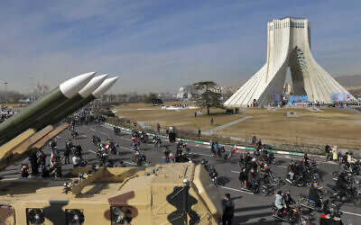 Iranians drive past missiles on motorcycles during a rally marking the 42nd anniversary of the Islamic Revolution, at Azadi (Freedom) Square in Tehran, Iran, Wednesday, February 10, 2021. (AP/Ebrahim Noroozi)