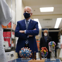 With a model of the Covid-19 virus displayed, President Joe Biden listens as Dr. Barney Graham, left, speaks during a visit at the Viral Pathogenesis Laboratory at the National Institutes of Health (NIH), Thursday, Feb. 11, 2021, in Bethesda, Md. Kizzmekia Corbett, an immunologist with the Vaccine Research Center at the NIH listens at right. (AP Photo/Evan Vucci)