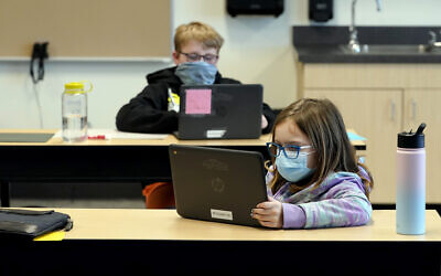 In this Feb. 2, 2021, file photo, students wear masks as they work in a fourth-grade classroom, at Elk Ridge Elementary School in Buckley, Washington (AP Photo/Ted S. Warren, File)