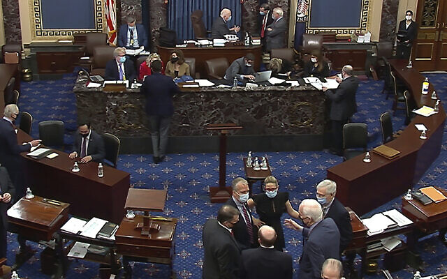 In this image from video, Republican senators and staff, lower right, talk on the floor after a vote on the motion to allow witnesses in the second impeachment trial of former President Donald Trump in the Senate at the US Capitol in Washington, Saturday, Feb. 13, 2021. (Senate Television via AP)