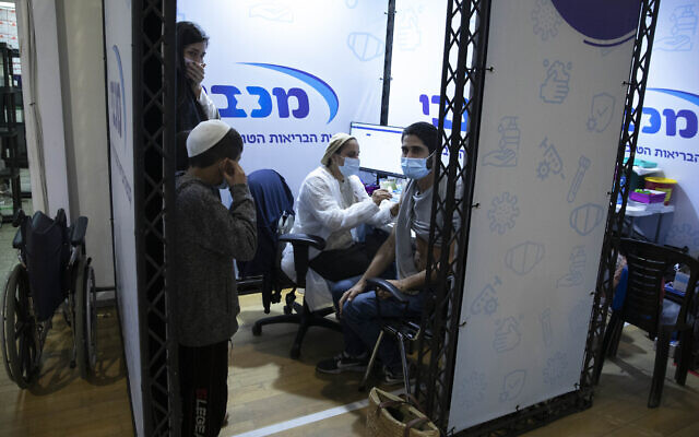 A man receives a Pfizer-BioNTech COVID-19 vaccine during an event to encourage the vaccination of young Israelis at a vaccination center in Holon, Feb. 15, 2021. (AP Photo/Sebastian Scheiner)