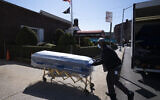 In this March 27, 2020 file photo, William Samuels delivers caskets to the Gerard Neufeld Funeral Home during the coronavirus pandemic in the Queens borough of New York (AP Photo/Mark Lennihan)