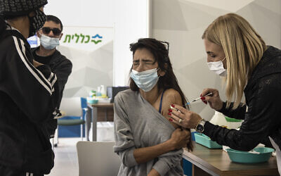An Israeli woman receives a Pfizer-BioNTech COVID-19 vaccine at a Clalit medical center in Dimona, Southern Israel, Sunday, Feb. 21, 2021. (AP Photo/Tsafrir Abayov)