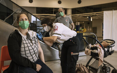 An Israeli paramedic from Magen David Adom medical services, administers a dose of the Pfizer-BioNtech COVID-19 vaccine to a woman at an Ikea store in Rishon Lezion, Feb. 22, 2021 (AP Photo/Tsafrir Abayov)