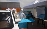 Workers show a drive-by voting station during a media tour demonstration of coronavirus measures prior to upcoming elections, at the central elections logistics center in Shoham, Israel, Tuesday, February 23, 2021. (AP/Sebastian Scheiner)