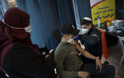 Israeli medical teams administer the coronavirus vaccine to Palestinians at the Qalandia checkpoint on Feb. 23, 2021 (AP Photo/Oded Balilty)