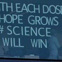 An employee works behind a window with a message taped to it at Pfizer Manufacturing in Puurs, Belgium on February 25, 2021. (Virginia Mayo/AP)
