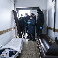 Relatives stand next to a coffin with the body of a patient who died from the coronavirus at a morgue of the regional hospital in Ivano-Frankivsk, 430 kilometers southwest of the capital, Kyiv, Ukraine on Feb. 26, 2021. (AP/Evgeniy Maloletka)