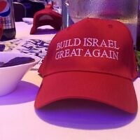 "Each table at Young Israel's gala dinner in 2019 was decorated by MAGA-style hats reading ""Build Israel great again."" (Ben Sales/JTA)"