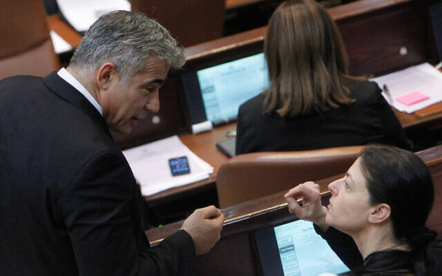 Yesh Atid chair Yair Lapid, left, speaking with Labor MK Merav Michaeli during a plenum session in the Knesset on June 5, 2013. (Miriam Alster/Flash90)