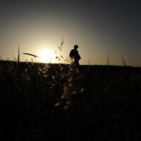 An IDF soldier seen silhouetted as he is walking through the fields near his army base, in Beersheba, southern Israel, March 31, 2014 (Mendy Hechtman/FLASH90)