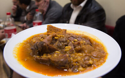 Illustrative. Ultra-Orthodox Jewish men eat cholent in Jerusalem, December 24, 2015 (Nati Shohat/Flash90)