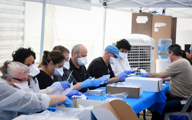 Illustrative: Israelis count the remaining ballots of voters under home quarantine after returning from Coronavirus infected zones, at a tent in the Central Elections Committee warehouse in Shoham, March 4, 2020. (Flash90)