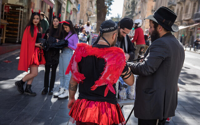An Israeli dressed up in costume ahead of the holiday of Purim, puts on tefillin in downtown Jerusalem, March 8, 2020 (Olivier Fitoussi/Flash90)