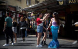 Israelis dressed up in costumes, as is customary during the Jewish holiday of Purim, seen in Tel Aviv, on March 10, 2020. (Miriam Alster/Flash90)