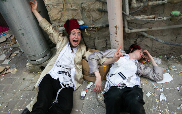 People celebrate the holiday of Purim in the ultra-orthodox Mea Shearim neighborhood in Jerusalem on March 11, 2020. (Olivier Fitoussi/Flash90)