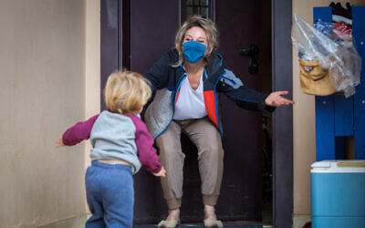 Illustrative: A grandson visits his grandmother at her home in Moshav Haniel in central Israel. She is wearing a face mask as a COVID-19 precaution. (Chen Leopold/Flash90)