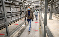 Palestinian workers enter Israel through the Mitar checkpoint in the West Bank city of Hebron, on May 5, 2020. (Wisam Hashlamoun/Flash90)