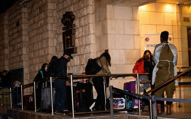 People who flew back to Israel seen arriving at the Dan Panorama Hotel used as a quarantine facility, on December 20, 2020. (Yonatan Sindel/Flash90)