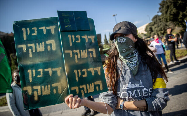 Sign reads 'The False Passport' as Israelis protest against the COVID-19 vaccine outside the Knesset in Jerusalem, January 4, 2021. (Yonatan Sindel/Flash90)