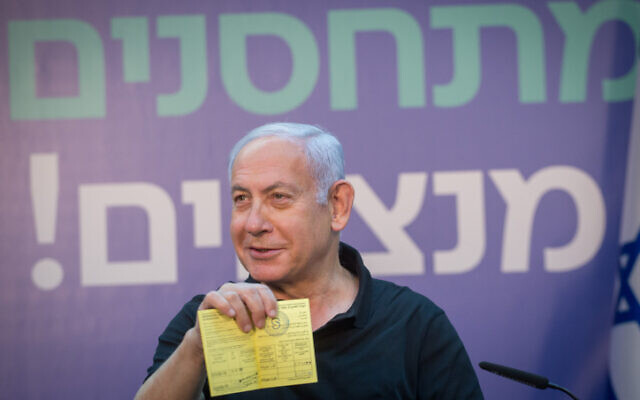 Prime Minister Benjamin Netanyahu receives a certificate after having his second COVID vaccine shot, on January 09, 2021. (Miriam Alster/Flash90)