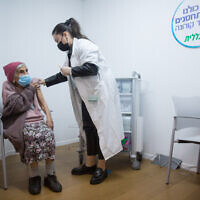 Illustrative: An elderly woman receives a COVID-19 vaccine, at a vaccination center in Tel Aviv, January 21, 2021 (Miriam Alster/Flash90)